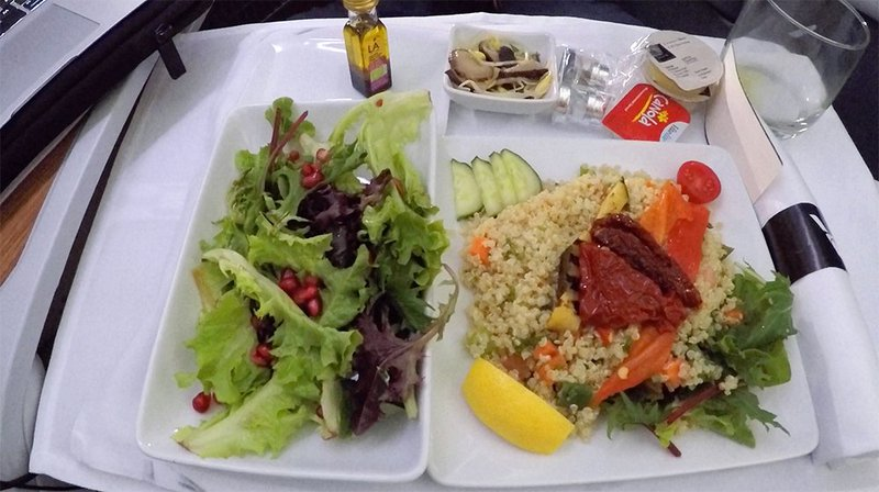 Healthy salad greens and pomegranate with a mediterranean couscous served aboard flight AA72.