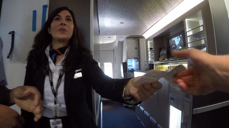 A friendly greeting from cabin crew aboard American Airlines flight AA72. The snack galley, visible on the right of this image, comes in handy on a long haul flight.